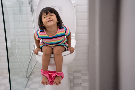 Foto per asian kid push it hard while sitting on toilet - Immagine Royalty Free