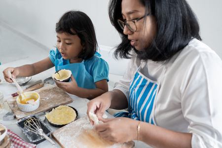 Photo pour mother and kid learning to make some dough - image libre de droit