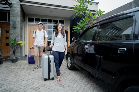 Photo pour couple put suitcases in to the car trunk - image libre de droit