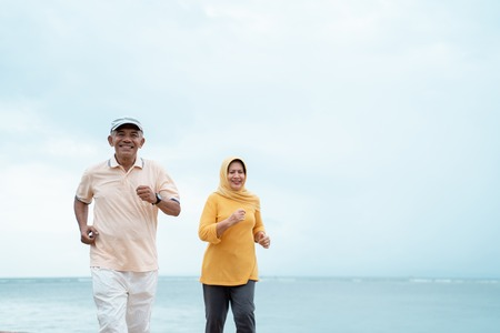Photo for senior man and woman together running on the beach - Royalty Free Image