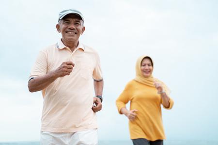 Foto de muslim old couple workout and running at the beach - Imagen libre de derechos