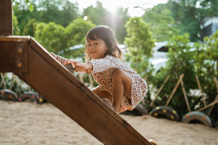 Foto per a girl enjoy playing on the wooden board climb alone - Immagine Royalty Free