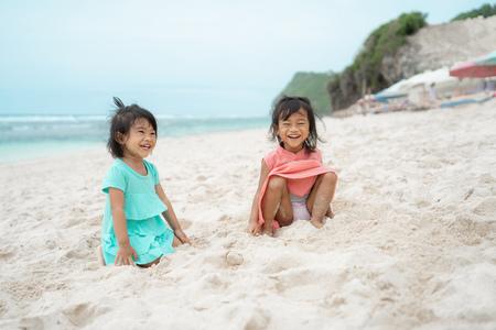 Foto de two daughter sit down on white sand smiling - Imagen libre de derechos
