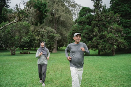 Foto de couple doing exercising by running in the garden - Imagen libre de derechos