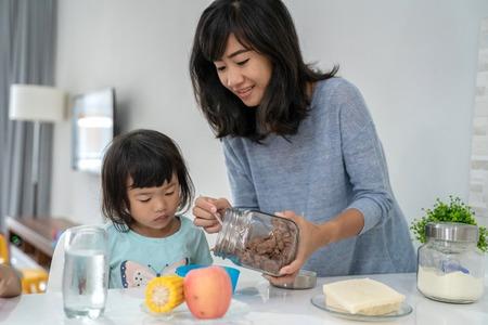 Photo pour mother preparing breakfast for her daughters - image libre de droit