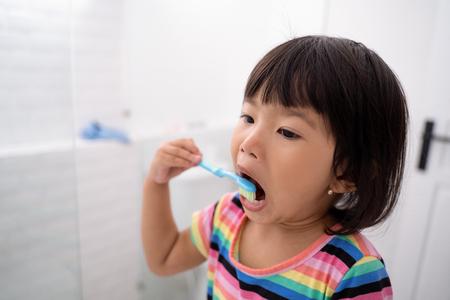 Photo pour portrait of a very smart little girl brush her teeth is a routine activities - image libre de droit