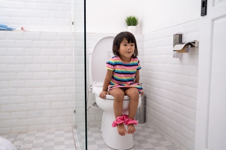Foto per asian toddler sitting on toilet with pants down - Immagine Royalty Free