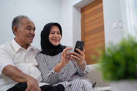 Photo pour mature asian couple using smartphone - image libre de droit