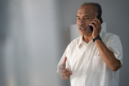 Photo pour a experienced businessman talking by phone using a smartphone to two way communication - image libre de droit