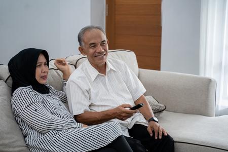 Photo pour asian muslim couple mature sitting couch relaxed when enjoy television - image libre de droit