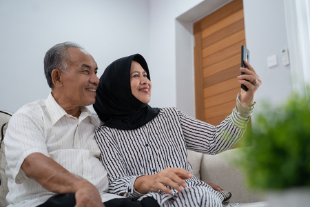 Photo pour mature couple taking selfie using smartphone - image libre de droit