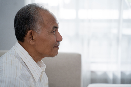 Photo pour closeup from side view of Asian old man sitting on the sofa - image libre de droit