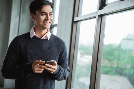 Photo pour Confident young businessman using cell phone - image libre de droit