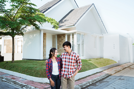 Photo pour asian couple standing in front of their new house - image libre de droit