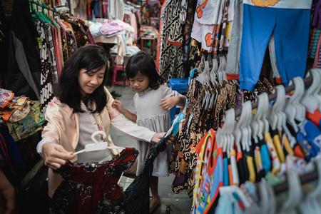 Photo pour mother buy and try batik for her daughter - image libre de droit