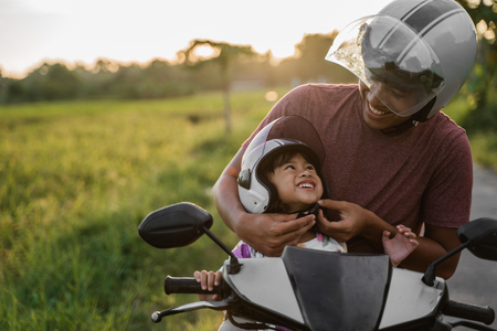 Photo pour daddy help her daughter to fasten the helmet - image libre de droit