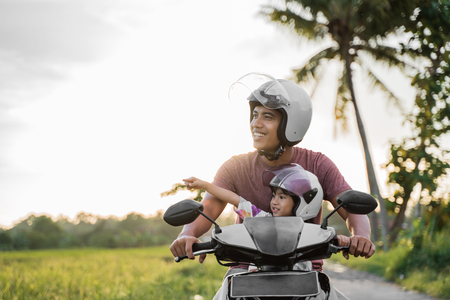 Foto de asian father and child  ride motorcycle scooter - Imagen libre de derechos