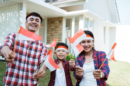 Photo pour family holding a flag of indonesia. celebrating independence - image libre de droit