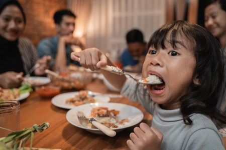 Photo pour child daughter eating by herself during dinner - image libre de droit
