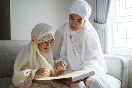 Photo for mother and kid reading quran - Royalty Free Image