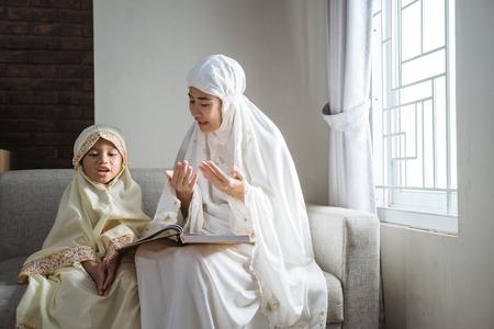 Foto de mother and kid reading quran - Imagen libre de derechos