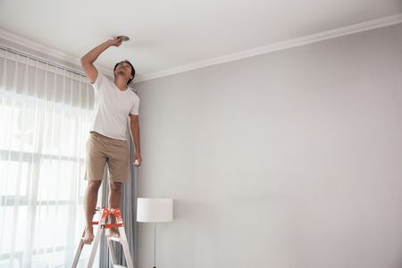 Photo for man using a stairs to install lights - Royalty Free Image