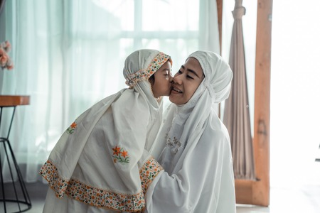 Photo pour muslim young child kiss her mom after praying - image libre de droit