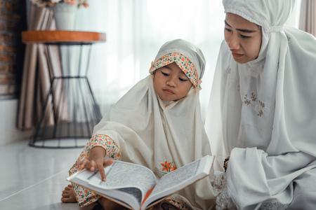 Foto de muslim parent and daughter reading quran - Imagen libre de derechos