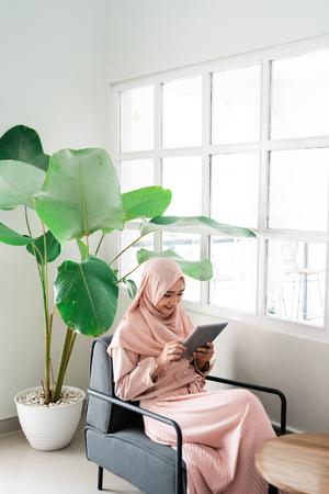 Foto de muslim woman browsing with tablet while relaxing - Imagen libre de derechos