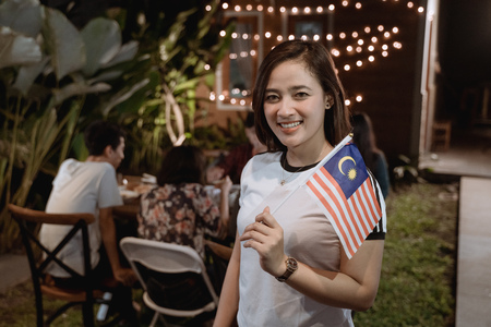 Photo pour asian woman holding malaysia flag while celebrating independence day - image libre de droit