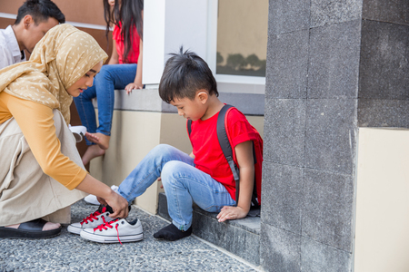 Photo pour happy asian mother with hijab help his son to put on his shoes - image libre de droit