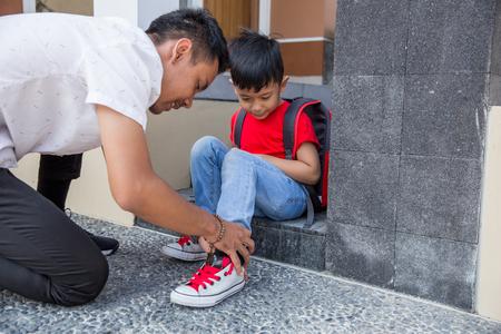 Photo pour help his son to put on his shoes - image libre de droit