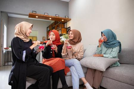 Photo pour Veiled young women enjoy together a fruits cocktail - image libre de droit