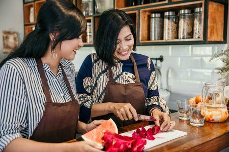 Photo pour Two asian woman cooking in the kitchen - image libre de droit