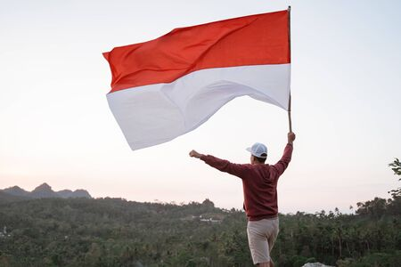 Photo pour man with indonesian flag of indonesia on top of the mountain - image libre de droit