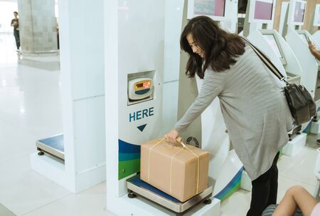Photo pour Asian woman take the cardboard on the luggage scale - image libre de droit