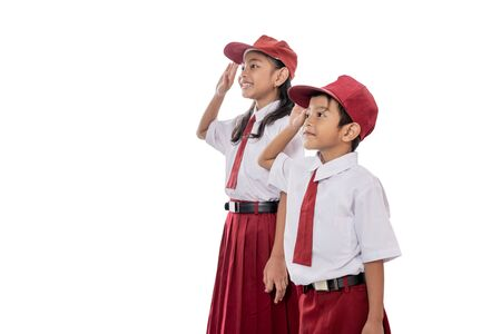 Foto de elementary student wearing uniform giving salute to indonesia flag - Imagen libre de derechos