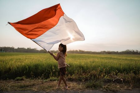Foto de asian little girl flapping Indonesian flag - Imagen libre de derechos