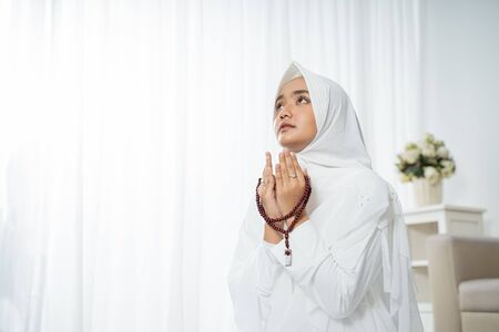 Foto de Muslim young woman praying in white traditional clothes - Imagen libre de derechos