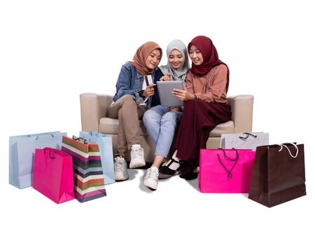 Photo pour Three veiled women while sitting near paper bags and holding credit card to buying at an online shop - image libre de droit