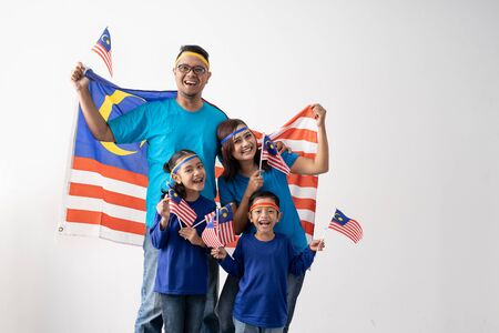 Photo for malaysian family holding malaysia flag over white background - Royalty Free Image