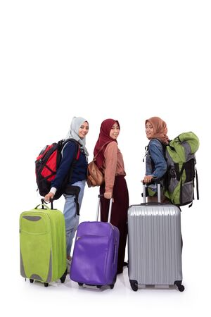 Photo pour Back view, three hijab woman standing holding suitcase and carrying bag - image libre de droit