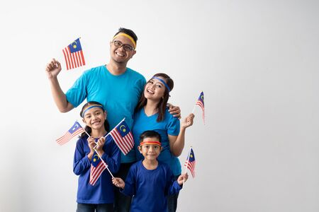 Photo pour malaysia family with attributes and flag celebrating - image libre de droit