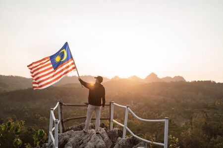 Photo for man with malaysian flag of malaysia on top of the mountain - Royalty Free Image