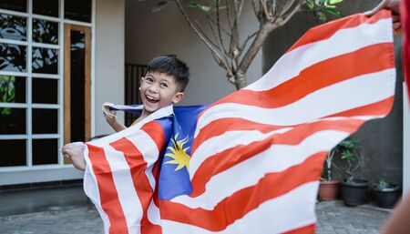 Photo for Malaysian kid with flag running - Royalty Free Image