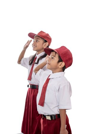 Foto per Elementary student wearing uniform giving salute to indonesia flag - Immagine Royalty Free