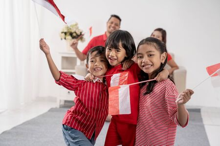 Photo pour Indonesian family holding indonesia flag over white - image libre de droit
