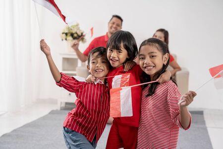 Foto de Indonesian family holding indonesia flag over white - Imagen libre de derechos