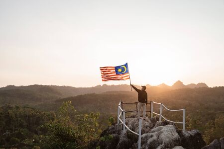 Photo pour asian man with malaysian flag of malaysia on top of the mountain - image libre de droit