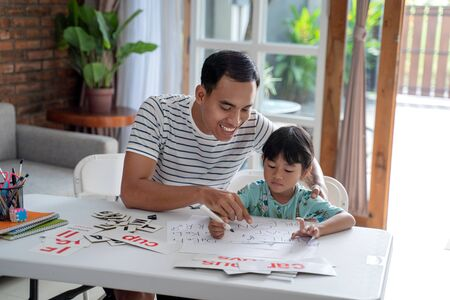 Foto de toddler studying with her father at home - Imagen libre de derechos